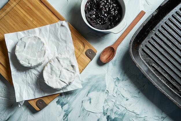 Zwei camembertkäsekopf auf weißem papier auf schneidebrett eine leichte textur tabelle.