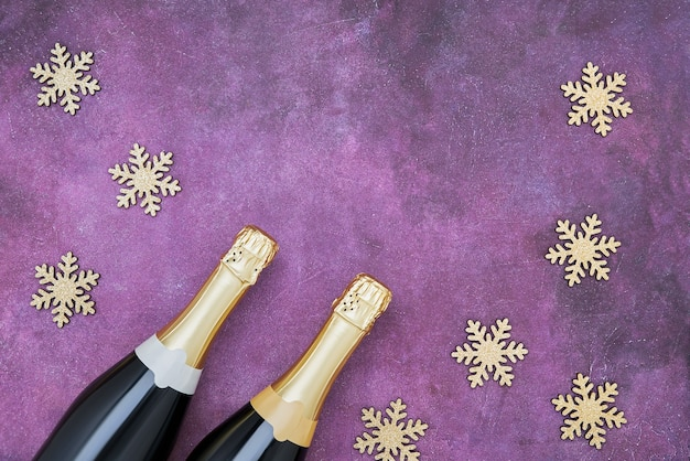 Zwei champagnerflaschen mit goldenen schneeflocken auf lila. flache lage des weihnachtskonzepts.
