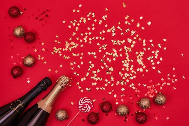 Zwei champagnerflaschen mit weihnachtsverzierungen auf rot.