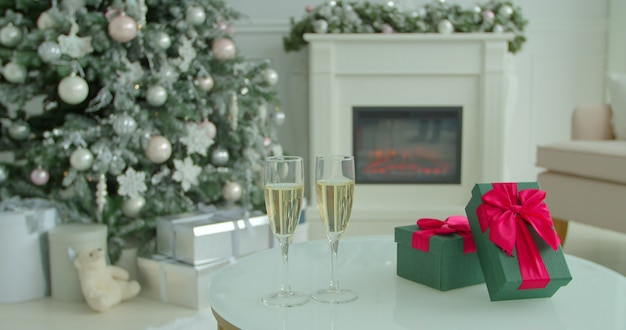 Zwei champagnergläser auf tisch am heiligabend mit weihnachtsbaum und deko im hintergrund.