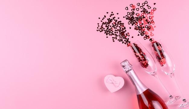 Zwei champagnergläser gefüllt mit herzförmigen pailletten mit einer flasche champagner und einem valentinstaggeschenk auf einem rosa hintergrund.