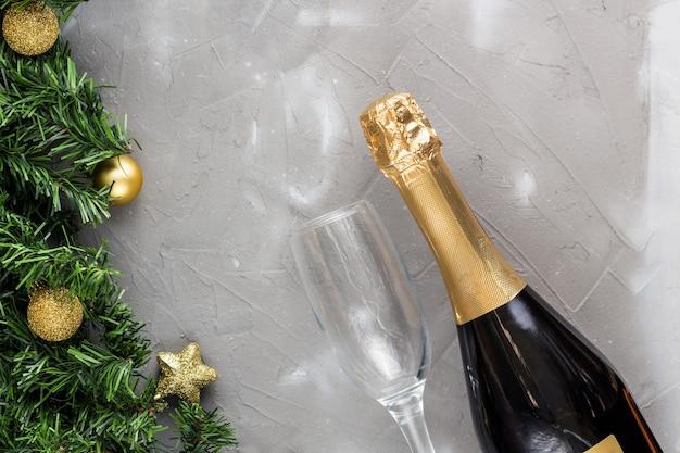Zwei champagnergläser mit goldenen kugeln und goldener champagnerflasche, grüner tannenbaum auf grauem hintergrund, kopienraum. festliche flache zusammensetzung für weihnachten oder neujahr.