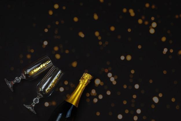 Zwei champagnergläser mit konfettis gegen bokeh auf schwarzem hintergrund.