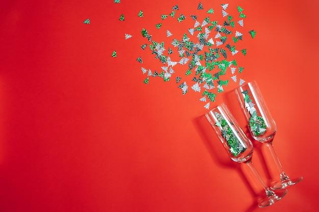Zwei champagnergläser mit spritzendem konfetti in form von weihnachtsbäumen auf rotem grund. neujahrs- und weihnachtskonzept. speicherplatz kopieren