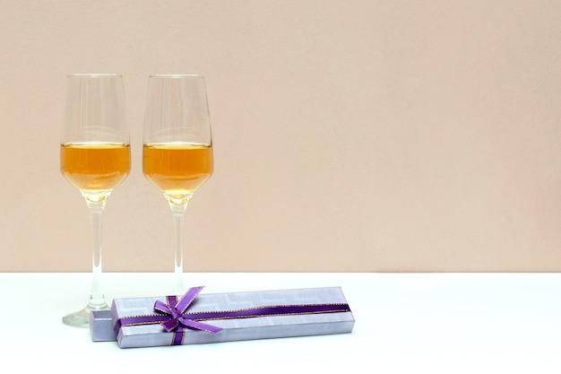 Zwei champagnergläser und geschenkbox am valentinstag, weiß mit kopienraum, liebeskonzept.