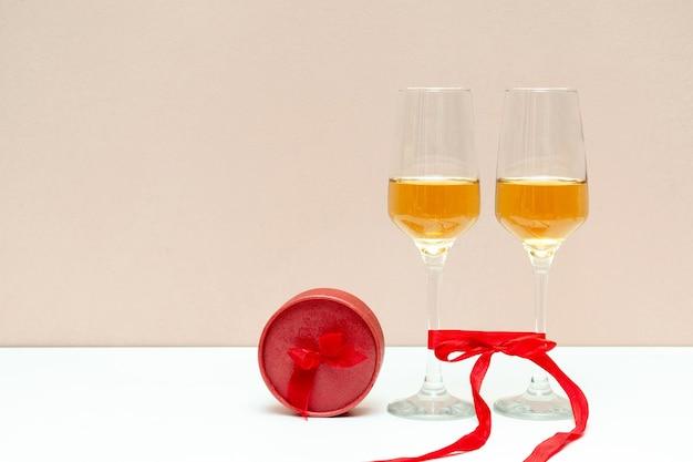 Zwei champagnergläser und rote schachtel als geschenk auf weiß mit kopienraum.