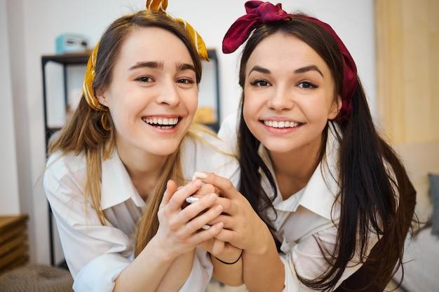 Zwei charmante aufgeregte junge freundinnen mit stirnbändern verbringen den tag zu hause, haben spaß und unterhalten sich