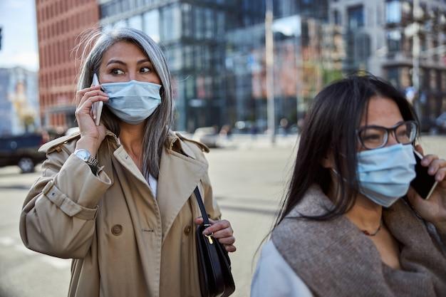 Zwei charmante frauen in medizinischen masken, die im freien telefonieren
