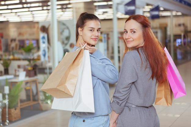 Zwei charmante freundinnen, die über ihre schultern in die kamera lächeln, während sie mit einkaufstüten im einkaufszentrum spazieren gehen