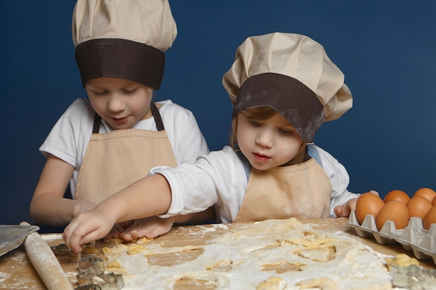 Zwei charmante kinder backen gebäck zusammen in der küche