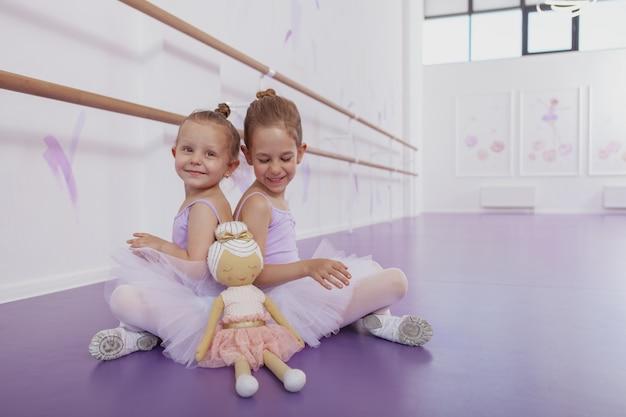 Zwei charmante kleine ballerinas sitzen rücken an rücken auf dem boden im tanzstudio