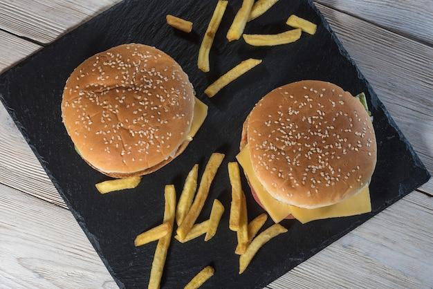 Zwei cheeseburger auf sesambrötchen mit saftigen rindfleischpasteten mit pommes-frites auf schwarzem schiefer.