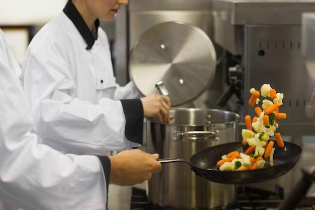 Zwei chefs, die in einer beschäftigten küche arbeiten