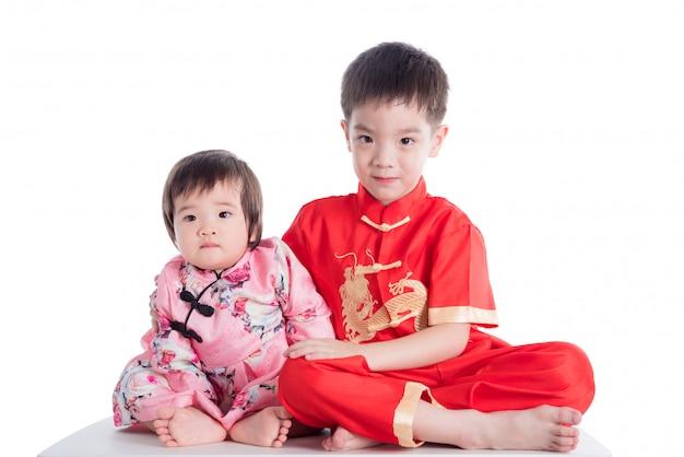 Zwei chinesische kinder, die das traditionelle kostüm sitzt über weißem hintergrund tragen