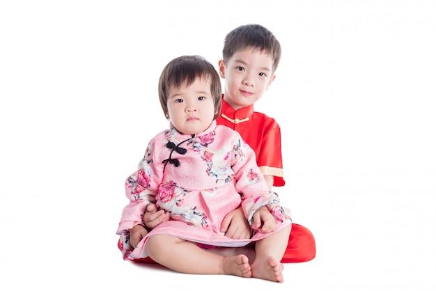 Zwei chinesische kinder, die traditionelles kostüm tragen, lächeln über weißem hintergrund