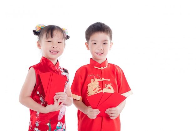 Zwei chinesische kinder im traditionellen kostüm, das rotes paketgeld und -lächeln hält