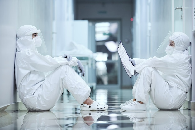 Zwei chirurgen in schutzanzügen sitzen im flur auf dem boden und untersuchen die krankenkarte des patienten