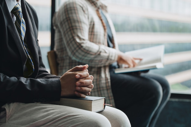 Zwei christen, die auf einem stuhl hält bibel sitzen und zusammen zu gott beten. der begriff des christentums.