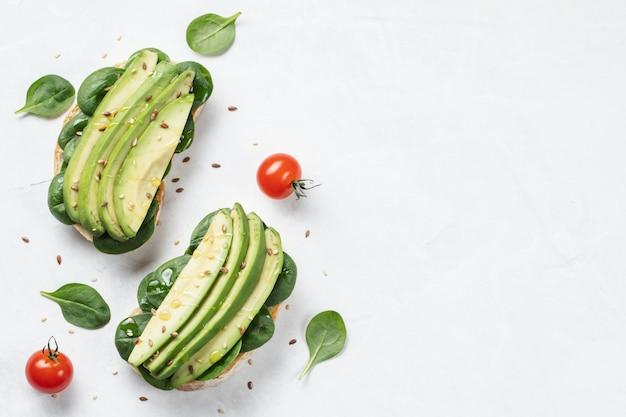 Zwei ciabatta-toast mit geschnittenem avocado-olivenöl, spinat, flachs und sesam.