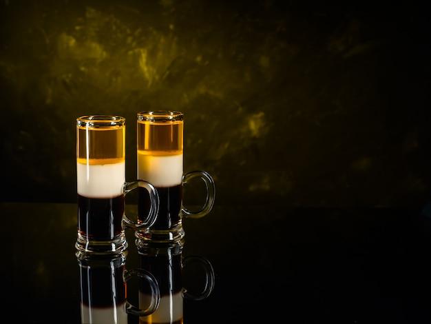 Zwei cocktails b-52 schossen auf schwarzer spiegeloberfläche und dunklem wandhintergrund