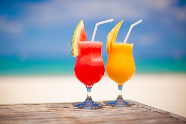 Zwei cocktails: frische wassermelone und mango auf dem hintergrund des atemberaubenden türkisfarbenen meeres