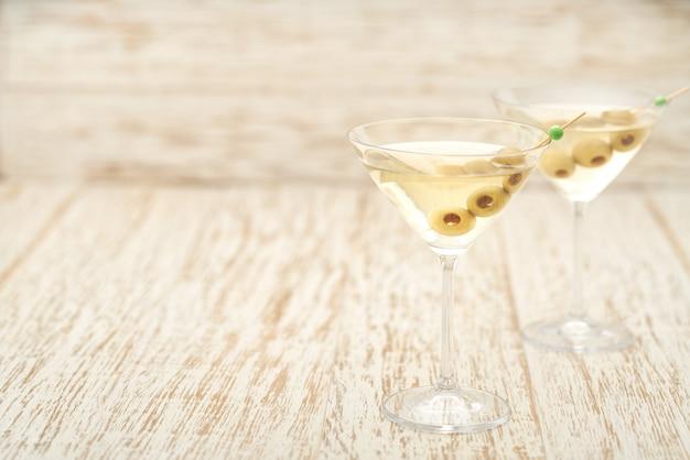 Zwei cocktails mit alkoholischem getränk und grünen oliven.