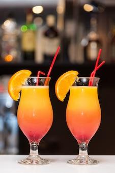 Zwei cocktails mit orangen stehen auf der theke