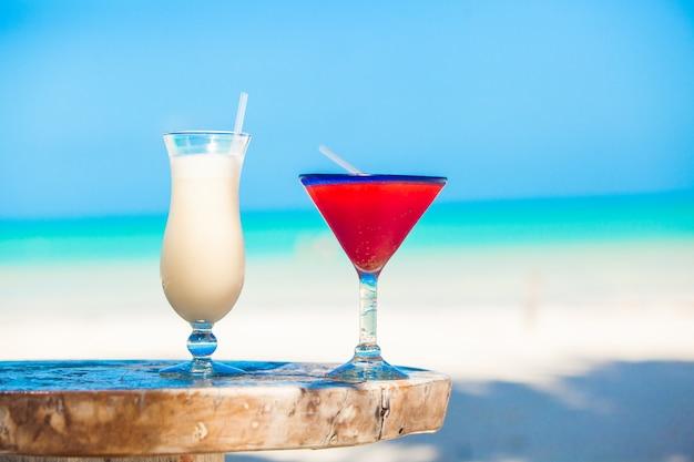 Zwei cocktails: pina colada und erdbeermargarita auf holztisch