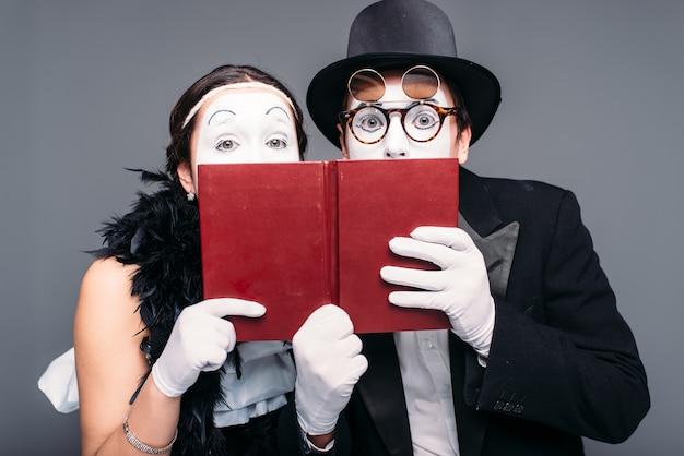 Zwei comedy-darsteller posieren mit buch. pantomime theaterschauspieler und schauspielerin auftreten
