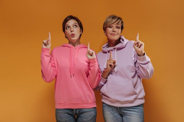 Zwei coole frauen mit kurzen haaren in rosa und lila breiten kapuzenpullis und jeans, die daumen oben zeigen und auf orange hintergrund posieren.
