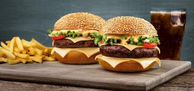 Zwei craft beef burger auf holztisch auf blauem hintergrund isoliert. im hintergrund steht ein glas mit einem getränk mit pommes