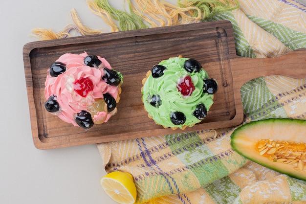 Zwei cremige cupcakes auf holzbrett.