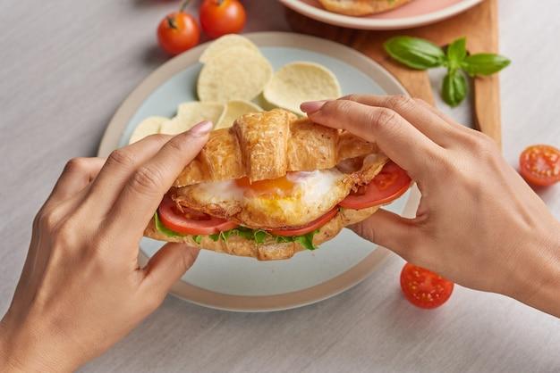 Zwei croissant-sandwiches auf holztisch, draufsicht