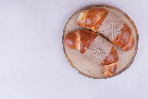 Zwei croissantbrötchen in papierverpackung auf holzbrett.
