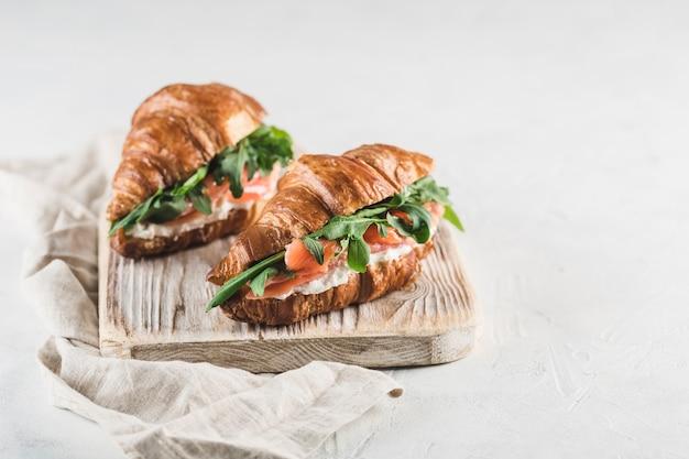 Zwei croissantsandwich mit lachs, ricotta und rucola auf einem holzbrett mit einer serviette