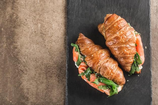 Zwei croissantsandwich mit lachs, ricotta und rucola auf einem schwarzen schiefer