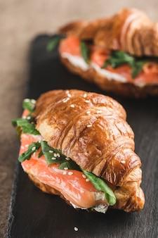 Zwei croissantsandwich mit lachs, ricotta und rucola auf einem schwarzen schieferbrett