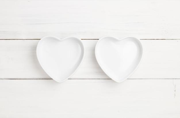 Zwei cup oder schüssel leeres herz-förmiges auf weißer hölzerner plankenbeschaffenheit für hintergrund.