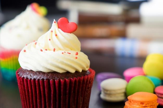 Zwei cupcake überstiegen mit valentinsgrußherzen mit macaron