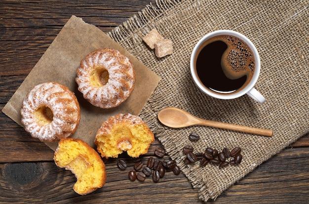Zwei cupcakes und eine kaffeetasse auf dem holztisch