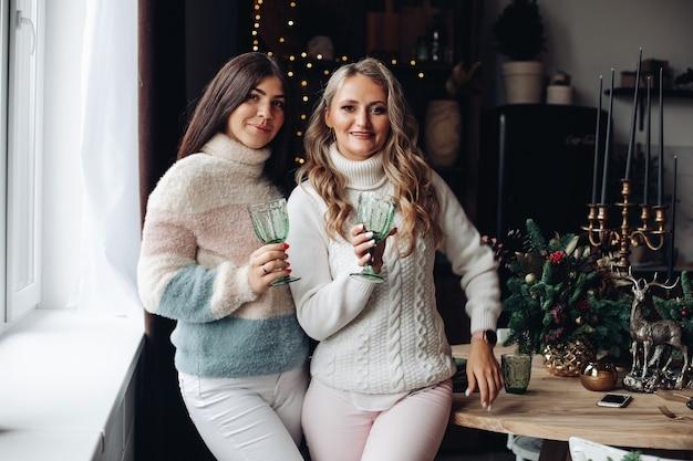 Zwei damen in bequemer winterkleidung, die eine schicke brille halten, während sie nahe beieinander stehen