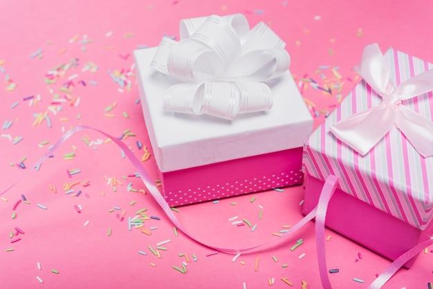 Zwei dekorierte geschenkboxen und streu bestreuen über den rosa hintergrund
