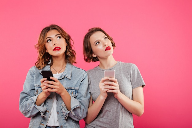 Zwei denkende damen, die telefonisch plaudern.