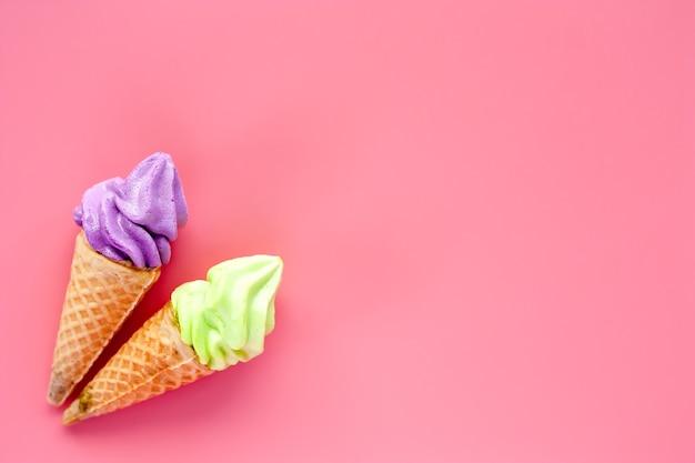 Zwei der eistüte auf rosa hintergrund für süßes und auffrischungsnachtischkonzept