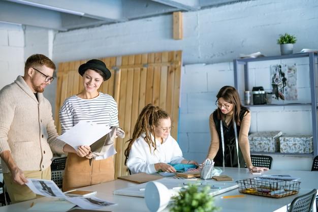 Zwei designer diskutieren neue skizzen von models, während ihre kollegen im hintergrund textilien auswählen