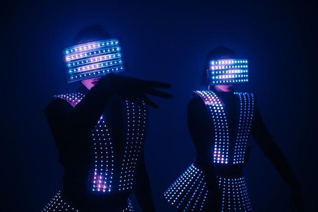 Zwei disco-tänzer bewegen sich in uv-kostümen.