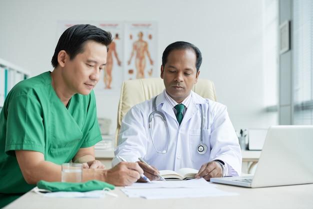 Zwei doctores, die am schreibtisch zusammensitzen arbeiten