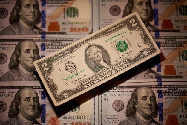 Zwei dollar auf einem unscharfen hintergrund von rechnungen im wert von hundert dollar die neue amerikanische rechnung.