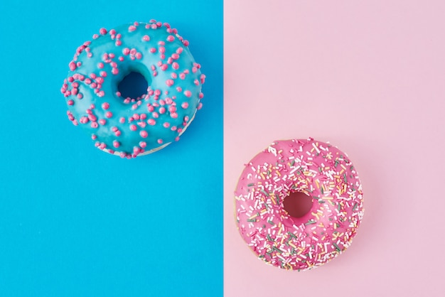Zwei donuts auf pastellrosa und blau. minimalismus kreative lebensmittelkomposition. flacher laienstil