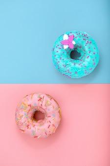 Zwei donuts auf pastellrosa und blauer oberfläche. minimalismus kreative lebensmittelkomposition. flacher laienstil